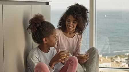 Happy african woman and her pleased little pretty daughter drinking juice while sitting on the floor near window at home