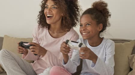 Cheerful african woman and her joyful little pretty daughter playing in game with joysticks while on bed at home