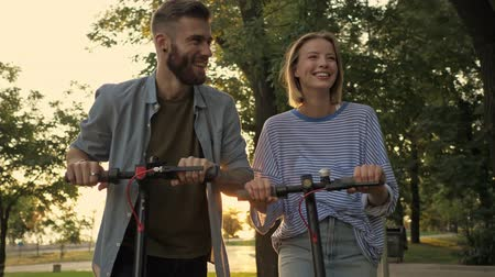 Деятельность выходные : A smiling young couple are laughing while driving electric kick scooters at green park landscape