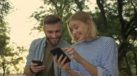 vyvažování : Young smiling girl is showing something on her smartphone to her boyfriend while sitting on the bench at a park landscape