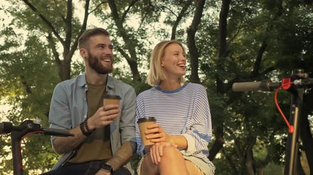 self driving : Young beautiful romantic couple with electric scooters is sitting on the bench at a park landscape Stock Footage