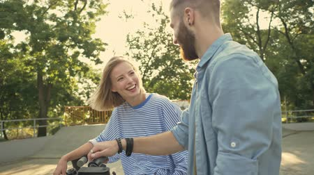 self balancing : An attractive happy young couple are talking while driving electric kick scooters on the sport area Stock Footage