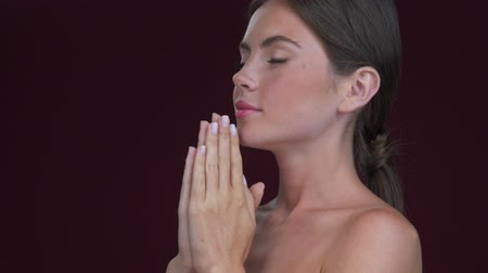 A side view of a nice calm young woman is standing in a praying pose isolated over dark red background Stock Footage