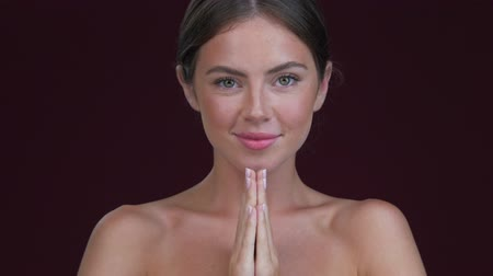 A nice calm young woman is holding hands like in a praying pose isolated over dark red background
