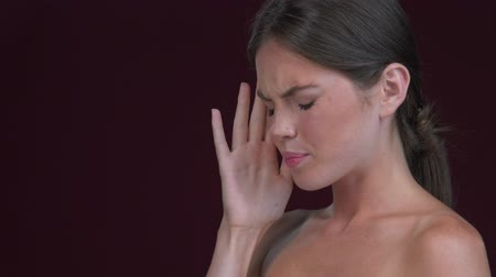 A side view of displeased young woman is touching her temples while feeling a headache isolated over dark red background