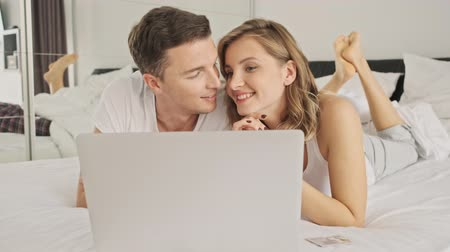 кровать : An attractive smiling young couple man and woman are using the laptop computer in a white bedroom in the morning