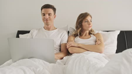 freio : A handsome boy is using a laptop computer while his girlfriend is sitting with crossed hands in a white bedroom in the morning Vídeos