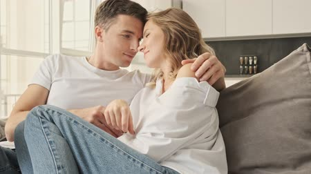 A caucasian couple man and woman in casual wear hugging together at home while sitting on sofa in living room Stock Footage