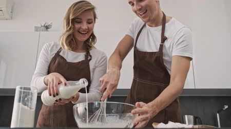 cozinhar : A happy smiling young couple man and woman are making dough together in the kitchen