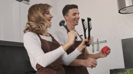jíst : A cheerful young couple man and woman are having fun while dancing and singing in the kitchen
