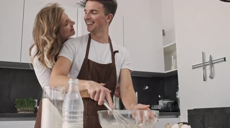 Lovely young couple man and woman wearing brown aprons are making dough together while hugging in the kitchen Stock Footage