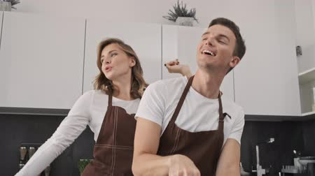 Positive smiling young couple man and woman wearing brown aprons are making dough while dancing in the kitchen Dostupné videozáznamy
