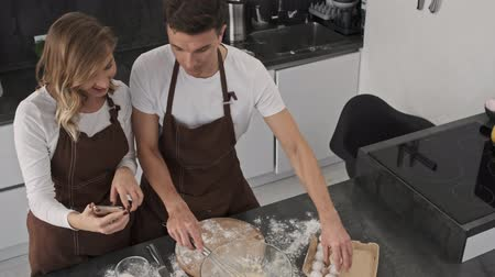 Top view of focused young couple man and woman wearing brown aprons are making dough while watching a recipe in the smartphone in the kitchen