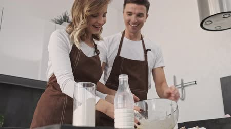 regozijo : Rejoicing young couple man and woman wearing brown aprons are making dough together in the kitchen