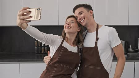 dinlenmek : Cheerful young couple man and woman wearing brown aprons are taking a selfie while cooking in the kitchen Stok Video