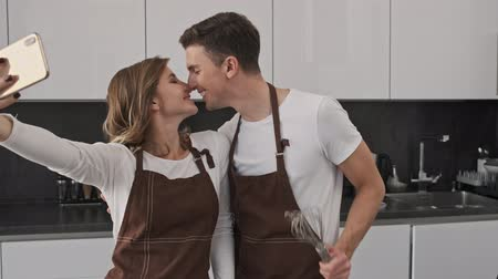 cozinhar : Lovely young couple man and woman wearing brown aprons are taking a kissing selfie while cooking in the kitchen