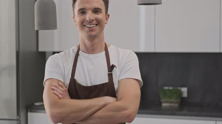 cozinhar : Smiling young man wearing a brown apron is crossing his hands while standing in a confident pose in the kitchen