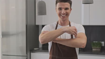 tek başına : Smiling young man wearing a brown apron is showing a thumb up to the camera in the kitchen