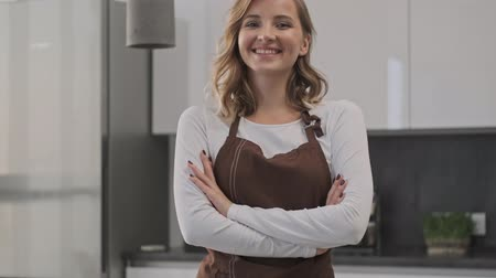 pocałunek : A beautiful young woman cook is sending an air kiss to the camera in the kitchen