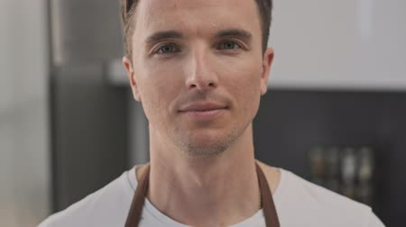 rejoice : Close-up view of a young man cook is smiling to the camera in the kitchen Stock Footage