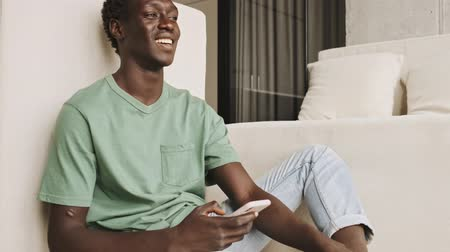 technics : A happy laughed african american man in casual clothes is watching something on his smartphone in the living room Stock Footage