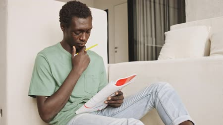 ödev : A pensive african american man in casual clothes is studying while holding a book and pencil in the living room Stok Video