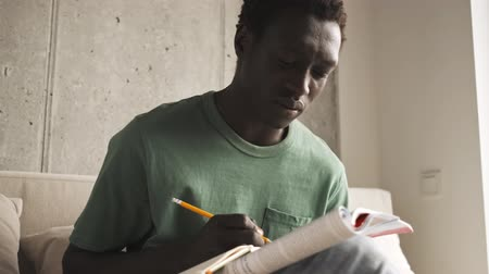 ödev : A calm focused african american man in casual clothes is making notes in a book while doing his homework in the living room Stok Video