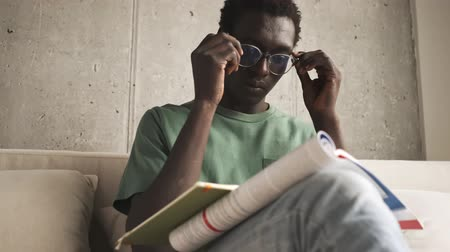 sofá : A calm handsome african american man in casual clothes is putting on his glasses while reading a book in the living room