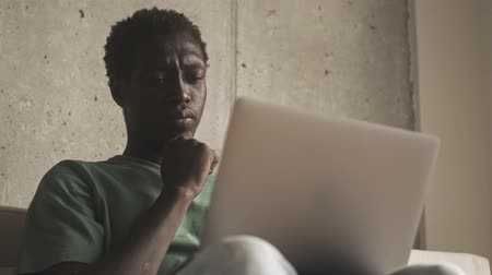 employed : A close-up view of a calm african american man is using his silver laptop computer in the living room Stock Footage