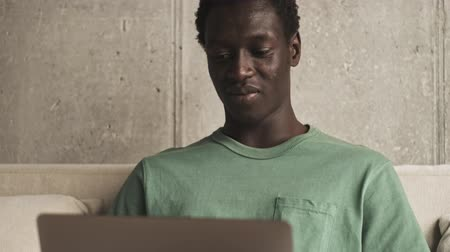 sofá : A happy young african american man is smiling while using his silver laptop computer sitting in the living room Vídeos