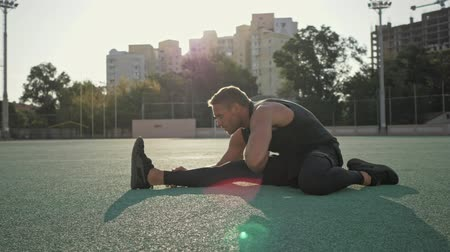 konkurenční : A good-looking young sportsman is going stretching at the stadium