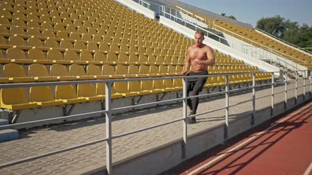 torso nudo : A strong serious young shirtless sportsman is running and jumping over the fence at the stadium