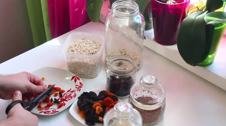uva passa : The man prepares the ingredients for muesli at home.
