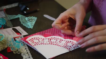 blue braid : The girl is engaged in making greeting cards at home. Using paper, lace, braid and other materials.