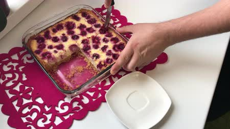 twaróg : A man cuts a curd cake with a knife, decorated with cherries. Then he puts a piece of cake on a plate. A cake in a glass form for baking. Wideo