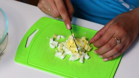majonez : Russian meat salad with vegetables and mayonnaise. A woman cuts a boiled egg on a cutting board.