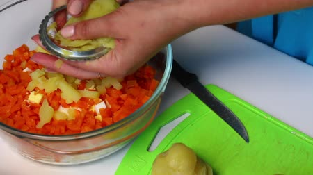 salatalık turşusu : Russian meat salad with vegetables and mayonnaise. A woman is cutting boiled potatoes.