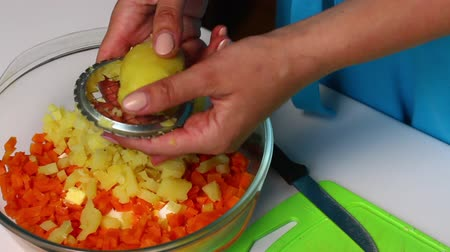 majonez : Russian meat salad with vegetables and mayonnaise. A woman is cutting boiled potatoes.