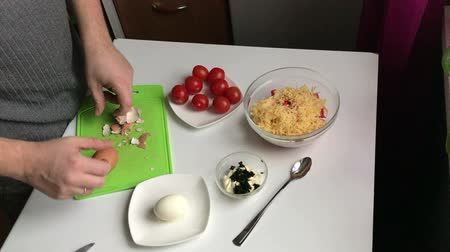boiled egg : A man cleans boiled eggs from the shell. Cooking salad of crab sticks, cheese, eggs and tomatoes.