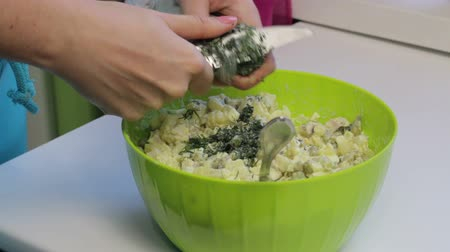 yemek tarifleri : A woman adds a dill to the salad. Cooking meat salad with eggs, potatoes, cucumbers and peas. Stok Video