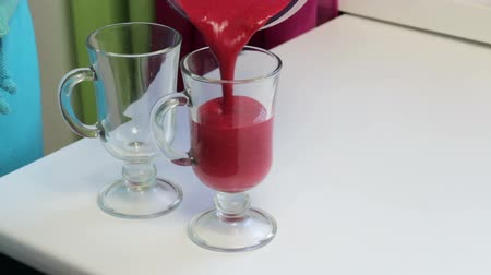 javul : A woman pours a cherry-banana smoothie into glasses.