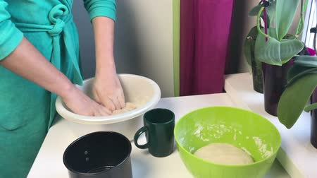 kneads : A woman kneads dough in her hands. Cooking bread at home.