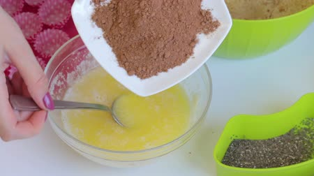 trufa : A woman drops cocoa powder into melted butter and mixes. For making sweets.