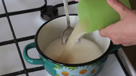 colander : A woman pours sugar into a pot and licks agar diluted in water. For making marshmallow.