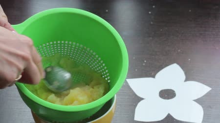 мята : A woman taps boiled apples into applesauce. Uses colander and spoon. For making marshmallow.