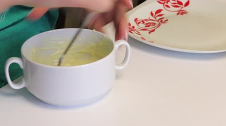 dyes : A woman adds a little white chocolate and mixes it. Cooking glazed for cake pops. Stock Footage