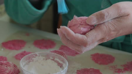 vörösáfonya : A woman applies powdered sugar on a marshmallow with a brush. Puts it aside.