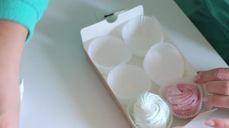 molho : Woman puts marshmallow in a gift box. Marshmallow different colors. Top view, close-up. Stock Footage