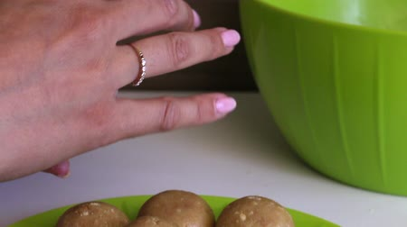 упакованный : Roll up balls of biscuits with condensed milk in her hands. Cooking basics for cake pops ..