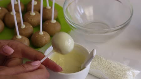 csomagolt : A woman dips a popcake billet into melted white chocolate. Spreads the glaze evenly Stock mozgókép